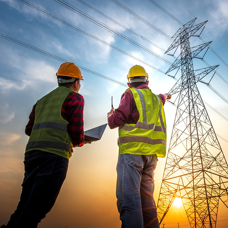 Two engineers in safety gear assess high-voltage power lines.