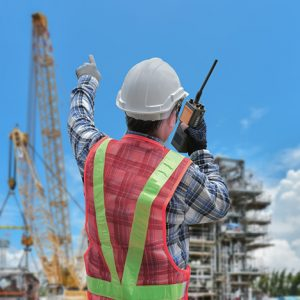 An engineer in a safety vest and hardhat coordinates a construction project.