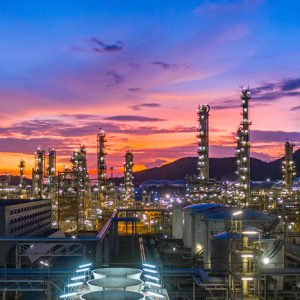 An oil refinery at sunset with mountains on the horizon.