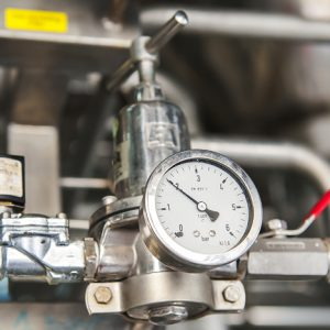 The dial of a pressure gauge registers a two near a red shut-off valve.