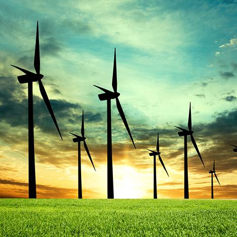 wind turbines in a field against a setting sun