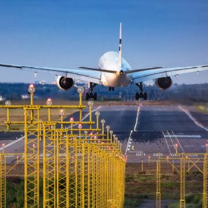 An airplane takes off from a runway near an electrical substation