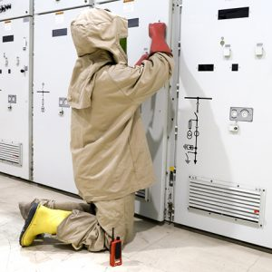 Worker in electrical PPE works on equipment